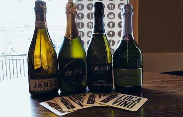 four sparkling wine bottles of Jansz, De Pró, Novecento, and Faire la Fête behind coasters monogrammed with Locavino logo